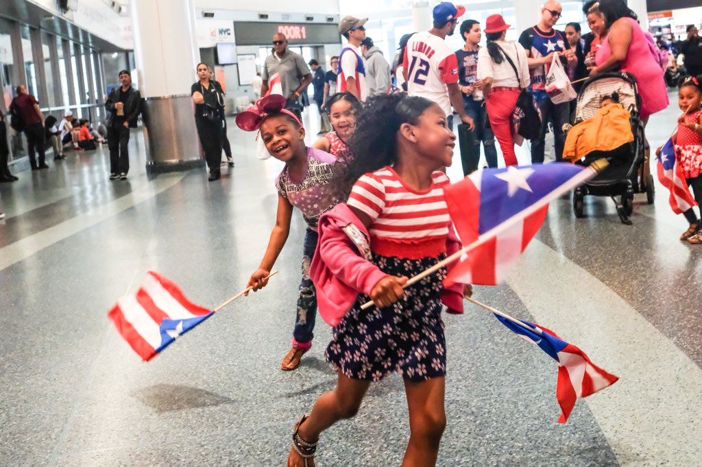 Three Children laugh at the ferry terminal waving flags of Puerto Rico.