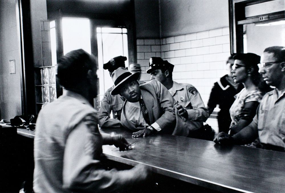 Black and white photograph of MLK sprawled across the police desk being restrained by two police officers as his wife and others look on.