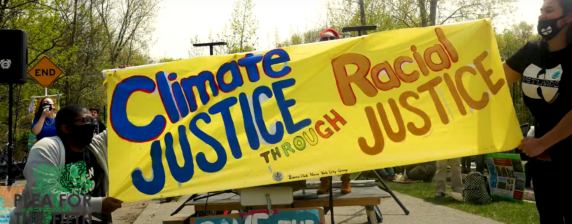 Two people holding either end of a yellow banner that reads Climate JUSTICE Through Racial JUSTICE in front of the stage.