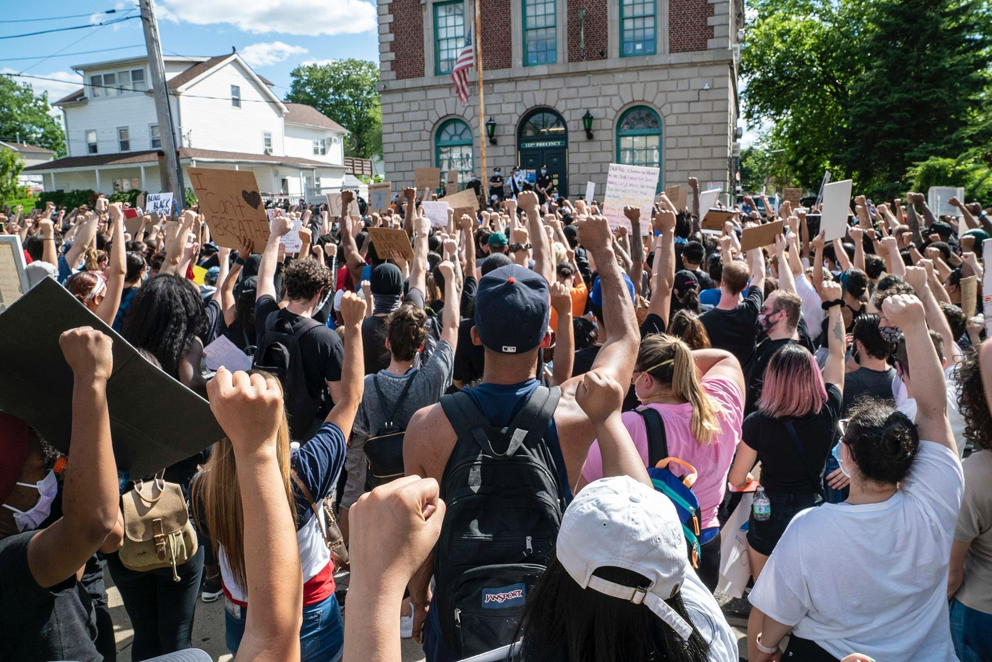 A very large crowd of people raise their fists in solidarity in front of a police station during a demonstration . Many of the demonstrators hold uo signs.
