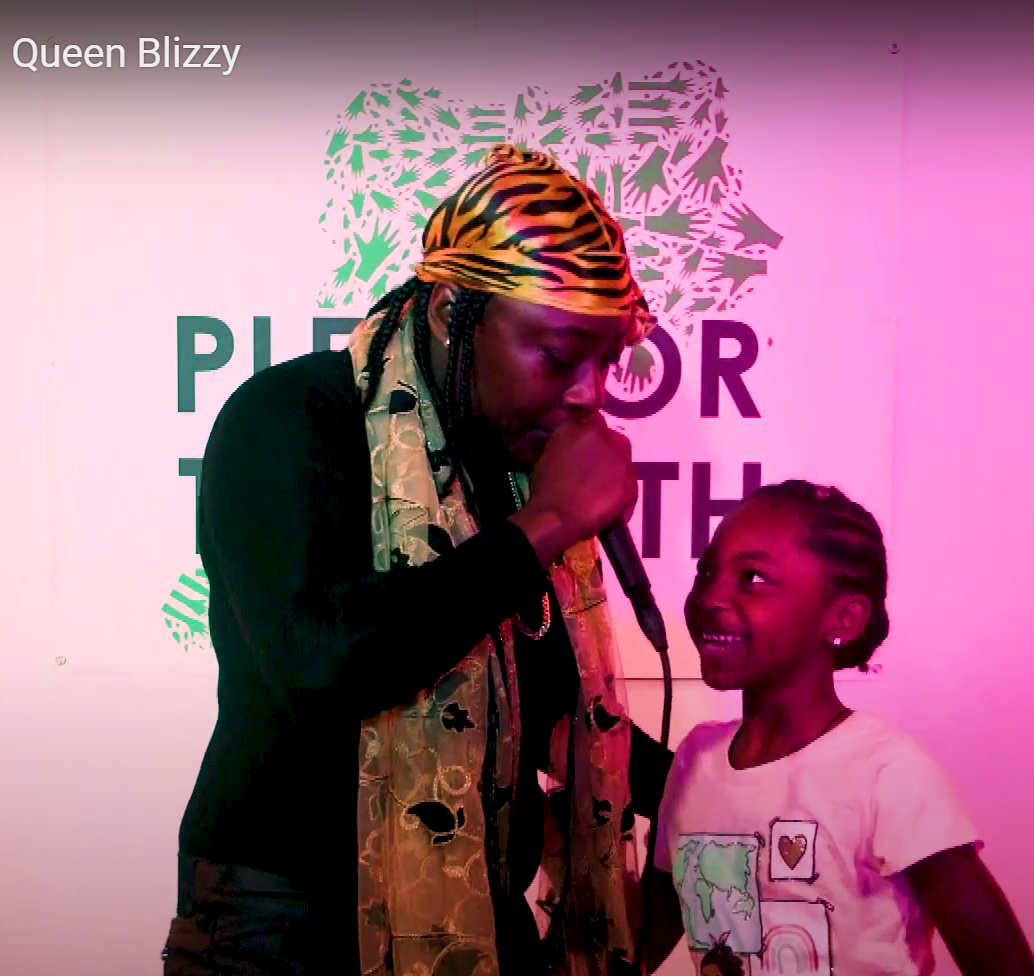A women wearing all black wirh a leopard print headwrap and gold scarf singing to a girl in a pink t-shirt. PFT5's logo in partially visible in the background.