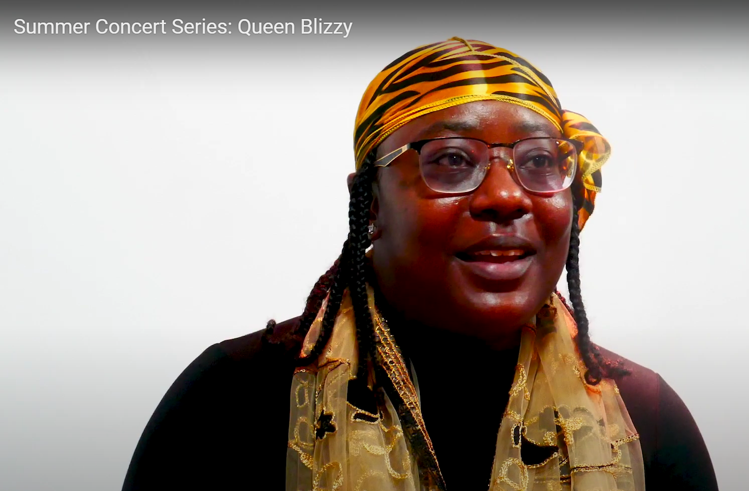 A black women wearing a black shirt with a leopard print headwrap and golden scarf.