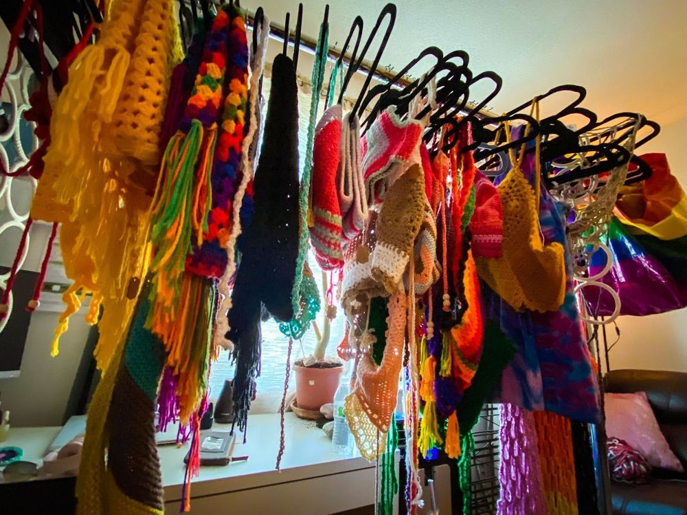 A clothes rack holding several crochet items in all different colors. Behind the clothes rack there is a white desk with a notebook and a plant.