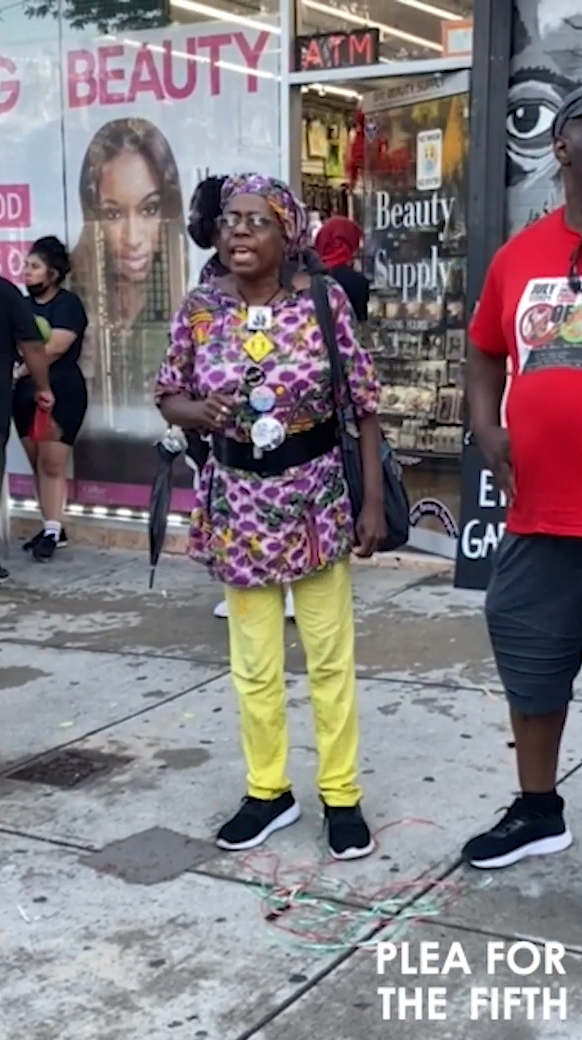 A women wearing yellow pants and a purple and black leopard print shirt in the middle of speaking. There a several buttons pinned to her t-shirt and she is wearing a headwrap.
